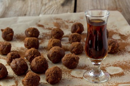 Small glass of cognac and homemade candies wooden table